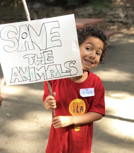 a child from inspired little activists preschool holds a sign to save the animals